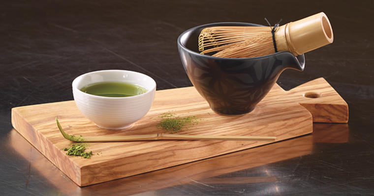 Matcha in a cup with bamboo whisk