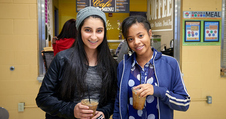 Two female students in a hallway holding cups of coffee