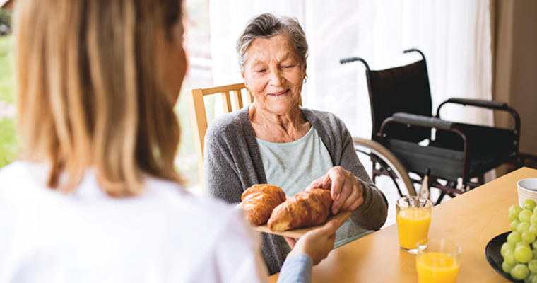 Healthcare foodservice worker presenting a plate of croissants to a senior care resident