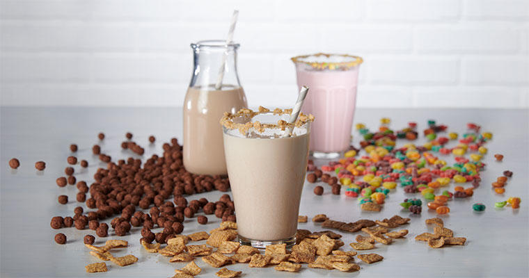 Cereal-infused milk with cereal scattered around the glasses