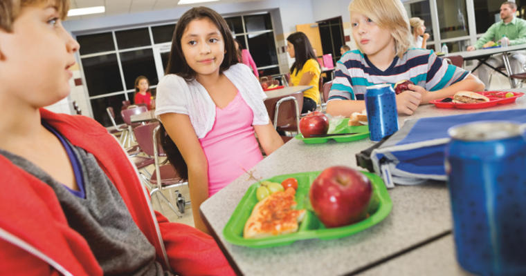 Students eating healthy foods in a cafeteria setting