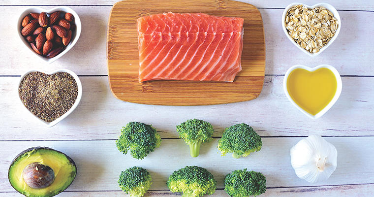 Salmon on a cutting board, cut broccoli spears and grains in heart-shaped containers