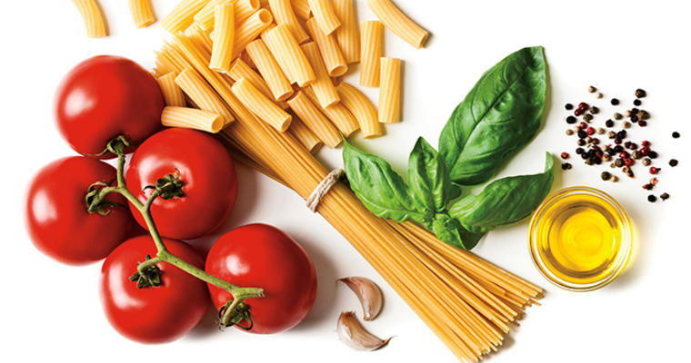 tomatoes, pasta, basil, oil, seasonings on a cutting board