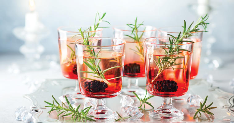 Five festive glasses filled with holiday drinks and an herbal garnish