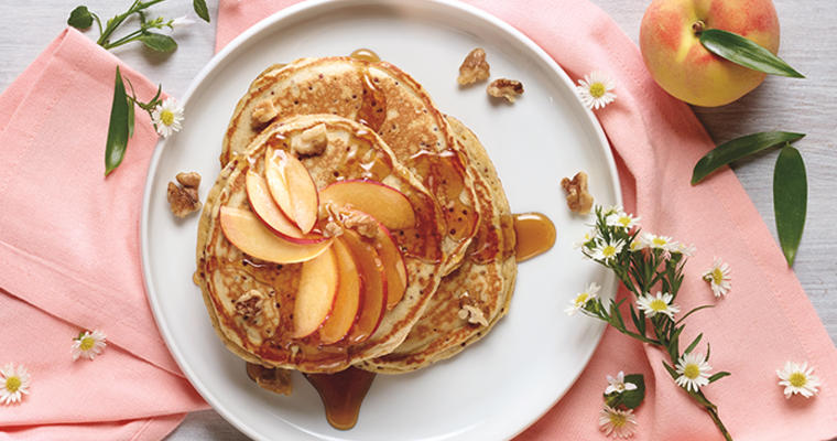 Quinoa pancakes covered with a swirl of peaches and maple syrup