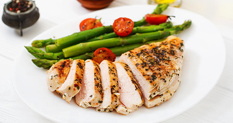 A sliced chicken breast on a white plate with asparagus spears