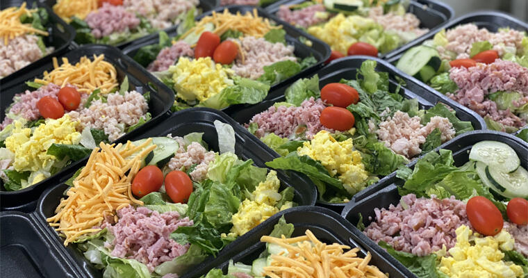 takeout cobb salads with ham, cheese, tomatoes, hard-boiled eggs and romaine lettuce