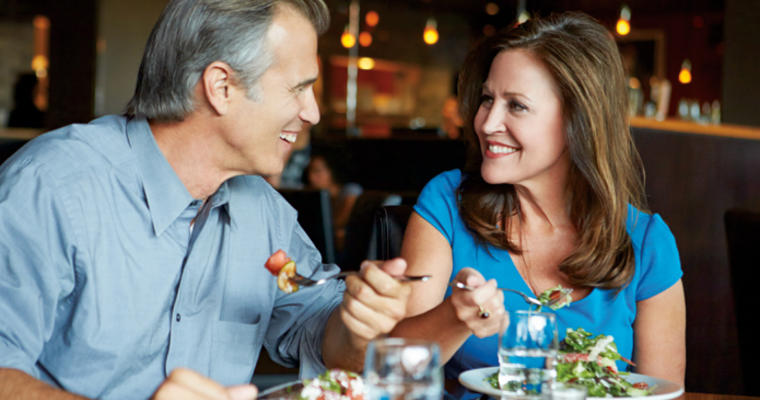 Middle aged man and woman eating