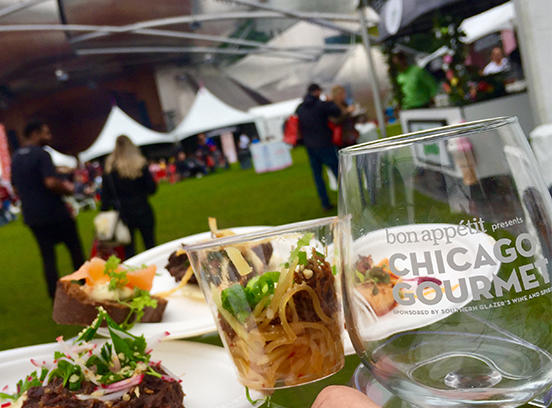 Wine glass with plates of food at chicago gourmet