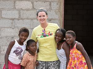 Volunteer posing with children from Zambia