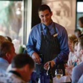 male waitstaff serving guests at restaurant